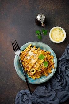 Вафли из кабачков с базиликом, петрушкой, сметаной и сыром в керамической тарелке на темном фоне бетона.