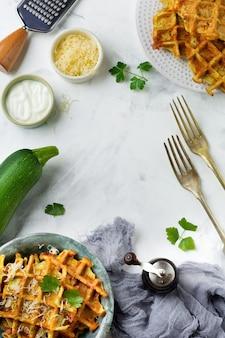 Вафли из кабачков с базиликом, петрушкой, сметаной и сыром в керамической тарелке на светлом фоне бетона Premium Фотографии
