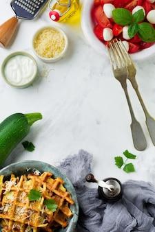 가벼운 콘크리트 표면에 세라믹 접시에 바질, 파슬리, 사워 크림 및 치즈가 들어간 호박의 웨이퍼