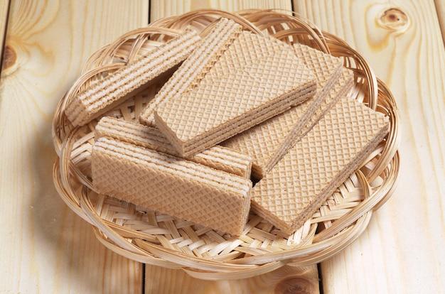 Вафли в плетеной тарелке на деревянном столе крупным планом