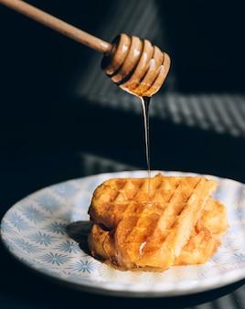 Вафли с медом на деревянном столе, в лучах утреннего солнца.