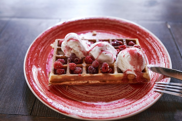 Waffeles with berries and ice cream on a wood table.  selective focus.
