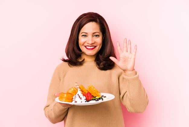 Женщина среднего возраста латинская держа waffle изолировала усмехаясь жизнерадостный показ 5 с пальцами.