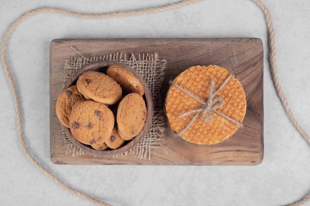 Вафля и миска печенья на белой поверхности. фото высокого качества