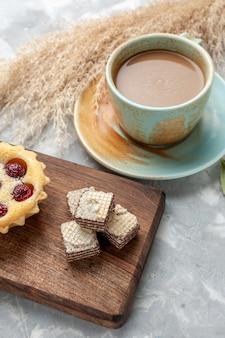 ライトグレーの机の上にミルクコーヒーとワッフルとケーキ、ケーキスイートシュガークッキービスケット