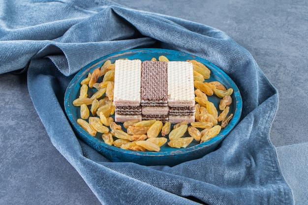 대리석 배경에 직물 조각에 나무 접시에 와플과 건포도. 무료 사진