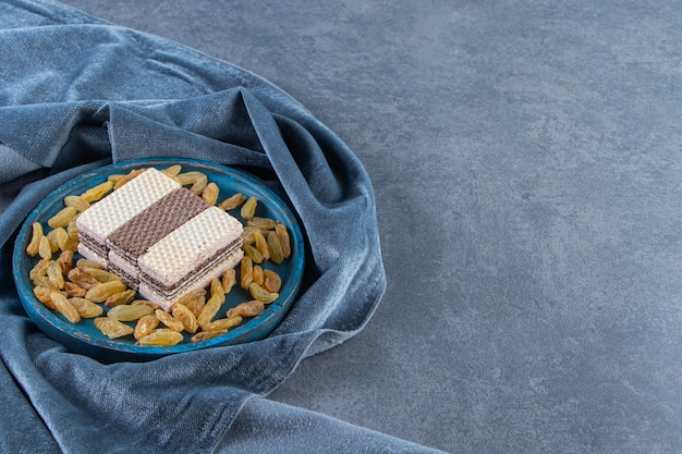 대리석 배경에 직물 조각에 나무 접시에 와플과 건포도.