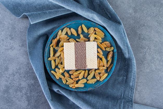 Вафли и изюм на деревянной тарелке на куске ткани на мраморной поверхности