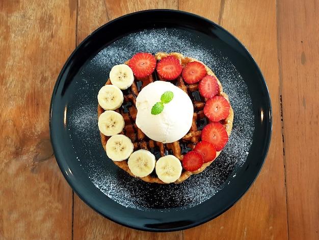 Вафельный банан и клубника с ванильным десертом из мороженого на деревянном фоне