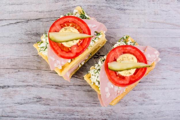 Вафельные, вареная колбаса, сыпучий сыр. вверху находится томатное кольцо и ломтик соленого огурца.