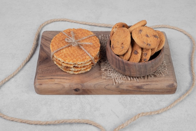 Waffle and bowl of cookies on white surface. high quality photo