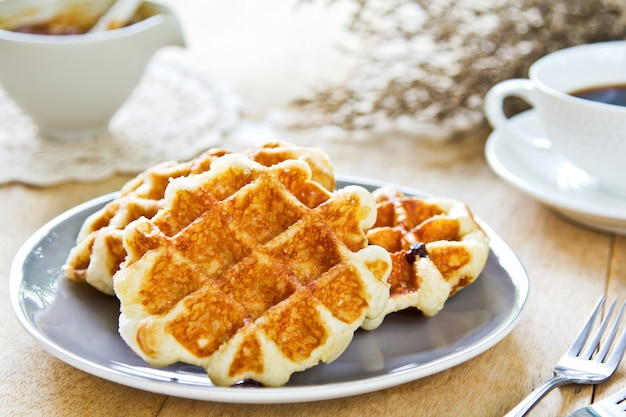 Waffle by caramel sauce and coffee