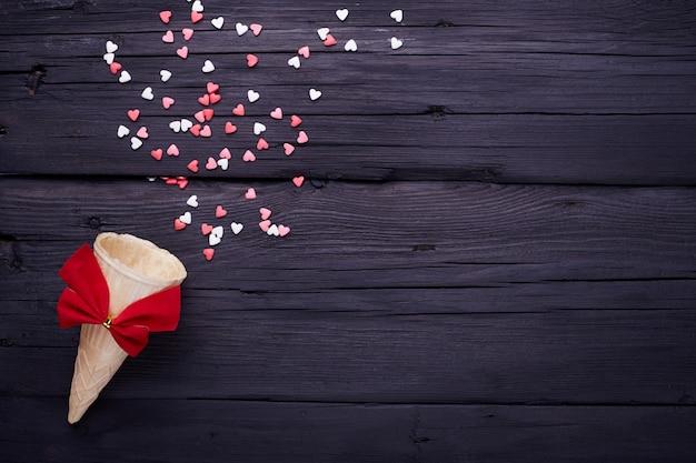 ワッフルコーンと黒の背景に小さなハートがたくさん。バレンタインデーのロマンチックな愛の背景