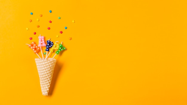 Waffle cone in the happy text candles with sprinkles on yellow backdrop