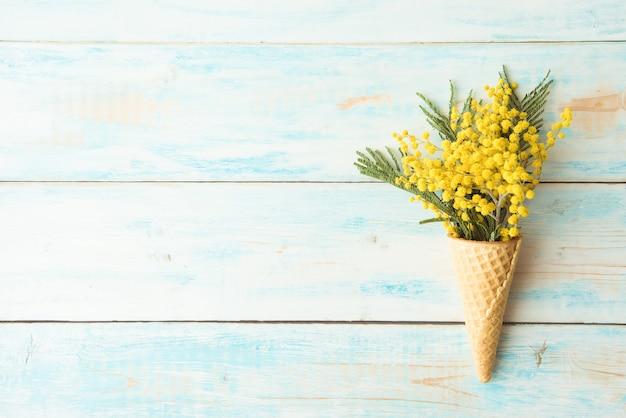 Конус вафли лежит на деревянном винтажном фоне. мимоза, весенний цветок. . копировать пространство