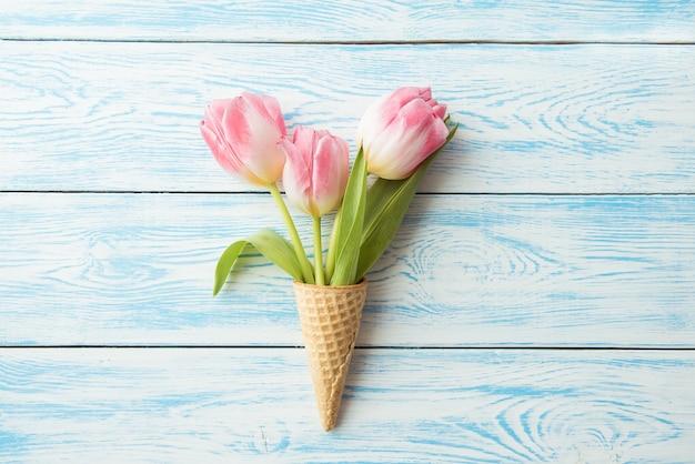 Конус вафли лежит на деревянном винтажном фоне. тюльпаны, весенние цветы