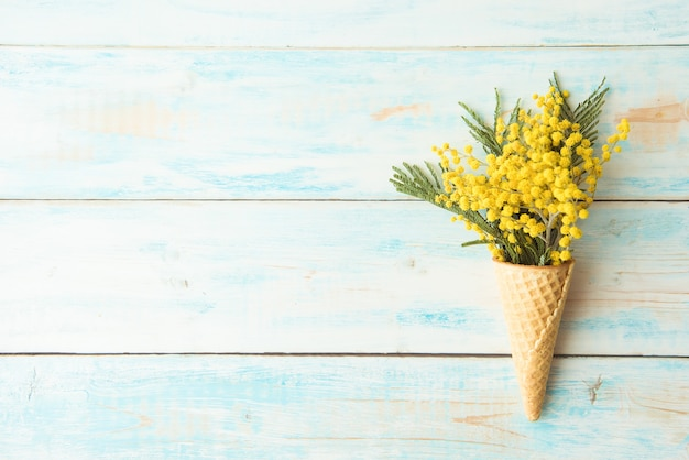 Waffle cone lies on a wooden vintage background. mimosa, spring flower. . copy space