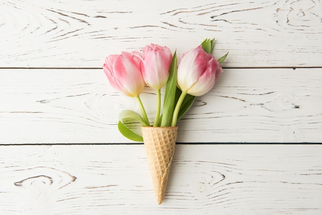 Waffle cone lies on a wooden vintage table. tulips, spring flowers