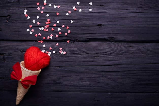 Waffle cone and lot of small hearts on black background. romantic love background for valentine's day