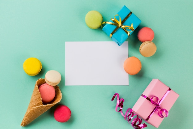 Waffle cone; macaroons; gift boxes near the white paper on mint green background