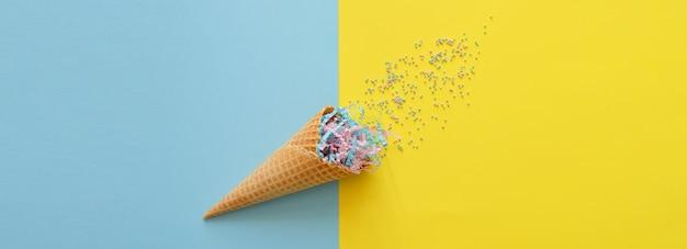 Вафельный рожок на ярко-желто-синем фоне с праздничной мишурой