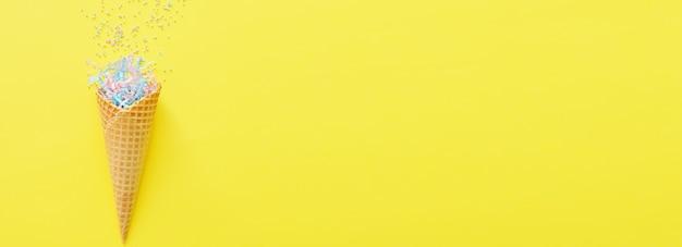 Вафельный рожок на ярко-желтом фоне с праздничной мишурой