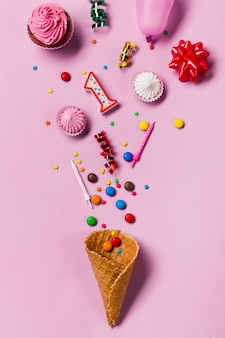 Waffle cone spilled from gems; sprinkles; candles streamers; balloon; gems and aalaw on pink background