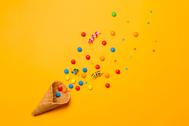 Waffle cone spilled from gems; sprinkles and streamers on yellow background