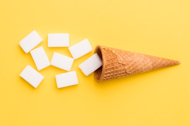Waffle cone and sugar on yellow background