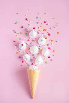 Waffle cone and white twisted meringue with confectionary decorations on pink background.