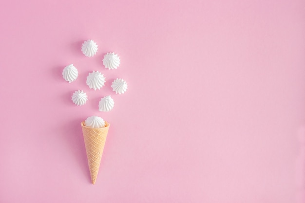 Waffle cone and white twisted meringues on pink background