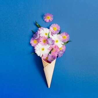 Waffle cone with chamomile flower bouquet on blue background. flat lay, top view