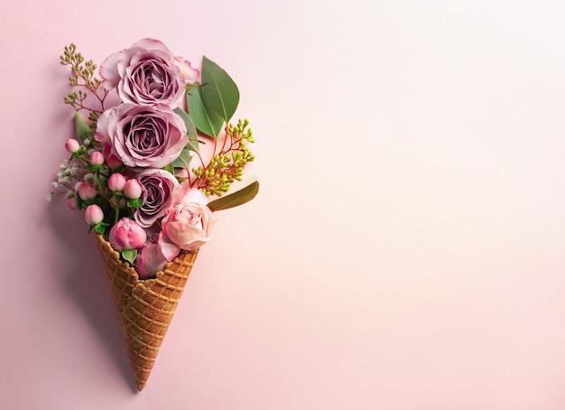 Вафельный рожок с композицией из цветов и веток на розовом