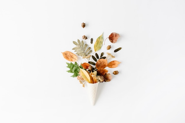 Waffle cone with dried autumn leaves bouquet on white