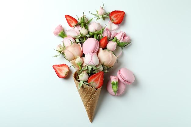 花、イチゴ、マカロンの白い背景のワッフル コーン