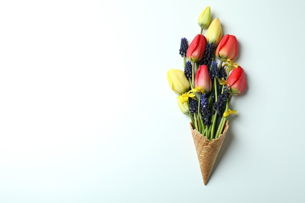 Waffle cone with flowers on white background