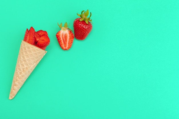 Waffle cone with fresh strawberries on vibrant background