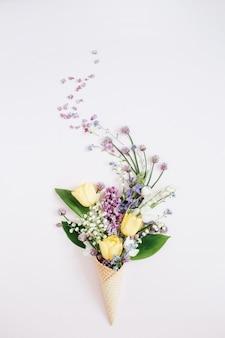 ライラックの花、スズラン、ピンクのチューリップの花束とワッフルコーン