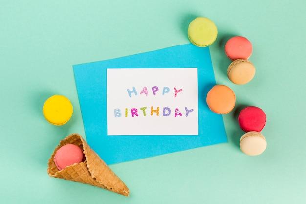 ミントグリーンの背景にお誕生日おめでとうカードの近くのマカロンとワッフルコーン