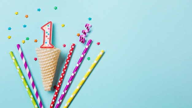 Waffle cone with number one candle; streamer and drinking straws on blue background