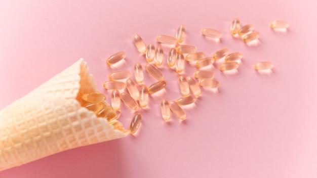 Вафельный рожок с капсулами омега-3 на розовом фоне. крупным планом, вид сверху. понятие о здоровье, витаминах, иммунитете