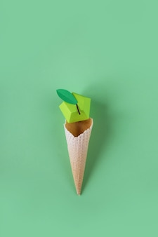 緑の表面に紙の果実とワッフルコーン