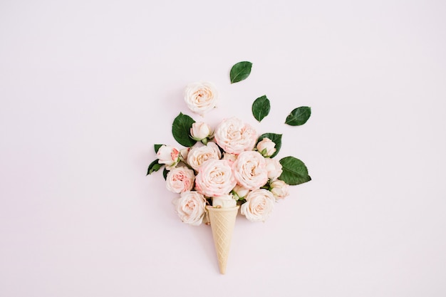 Waffle cone with pink bombastic roses bouquet on pale pastel pink