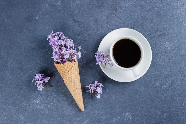 Waffle cone with purple lilac and cup of black coffee on dark blue stone concrete table background.