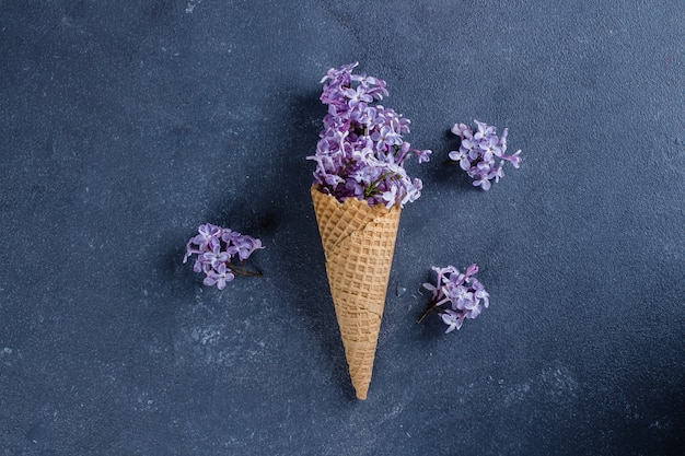 Waffle cone with purple lilac on dark blue stone concrete table background. flat-lay, top view