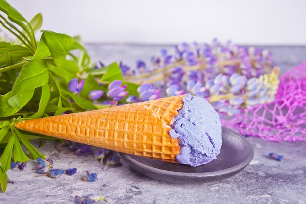 Waffle cone with purple lilac ice cream on the dark gray background decorating lupins