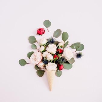 Вафельный рожок с красными, бежевыми розами и букетом эвкалипта на бледно-пастельно-розовом