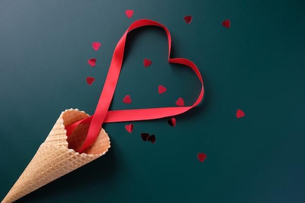 暗い背景にバレンタイン要素とワッフルコーン。バレンタインデーのコンセプト。ハートの形をした赤いリボン。バレンタイン・デー