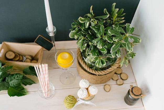 Вафельный рожок с белым мороженым в стеклянной вазе, бумажные тубы и растение в вазе на кухонном столе или в кафе, вид сверху