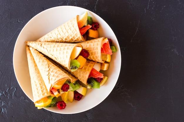 Вафельные рожки с нарезанными свежими фруктами на белой тарелке. вид сверху.